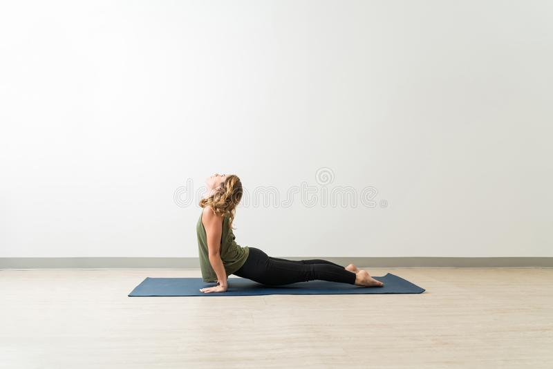 Female With Upward Facing Dog Pose On Mat In Studio royalty free stock image