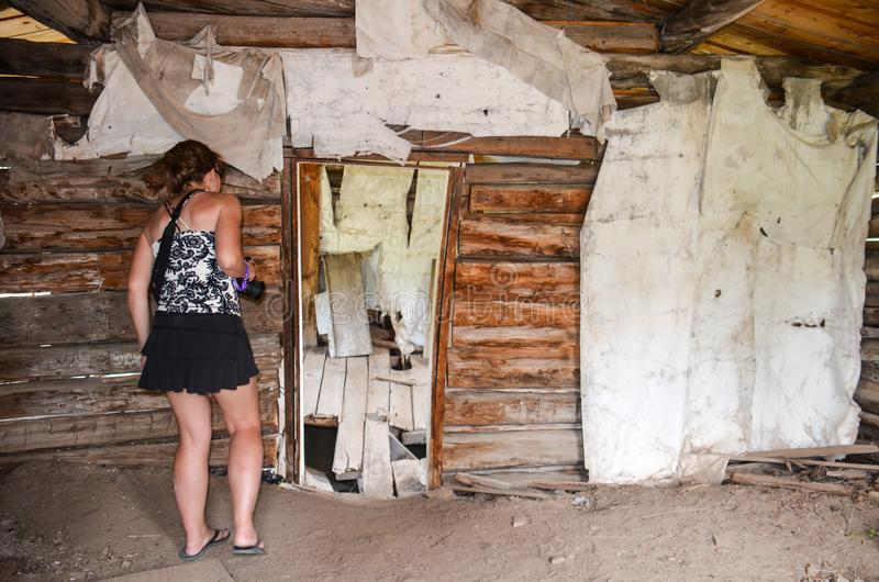 Female urban explorer investigates an abandoned building interior in Miners Delight Wyoming. Female urban explorer investigates an abandoned building interior in royalty free stock photo