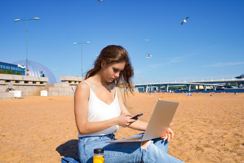 Female using apps on cellphone during distance work on notebook device royalty free stock photography