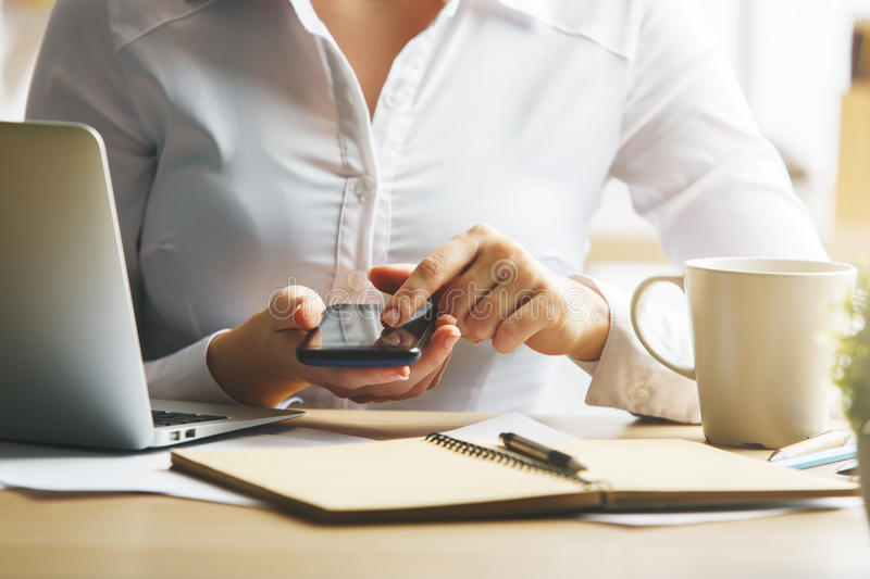 Female using smartphone. Close up of female hands using smartphone above desk with notepad, coffee cup and laptop stock images