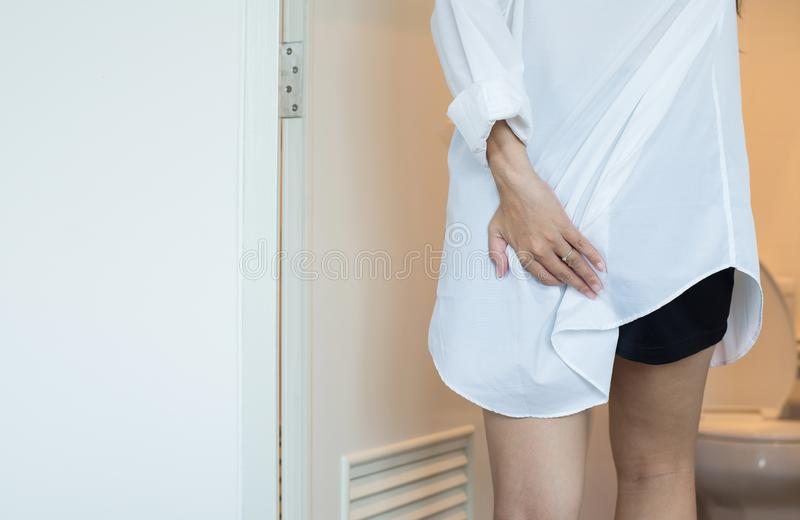 Female using toilet and suffers from Diarrhea and Hemorrhoids after wake up in morning at home,Copy space for text. Woman using toilet and suffers from Diarrhea stock photography