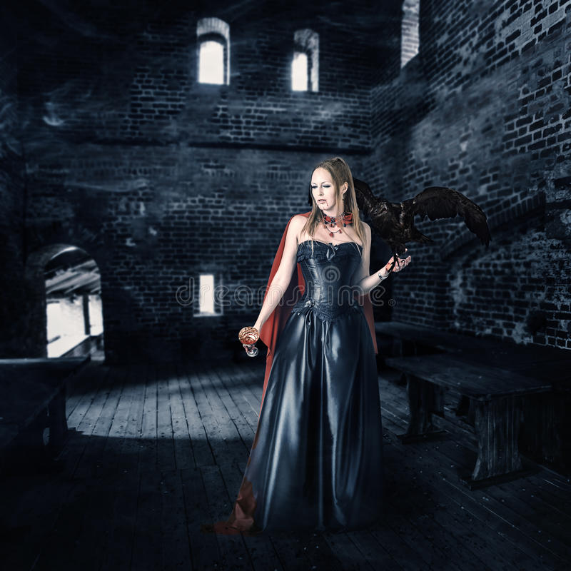 Female vampire with cup of blood in old castle. Young beautiful female vampire aristocrat with a cup of blood stands in the old castle royalty free stock photo