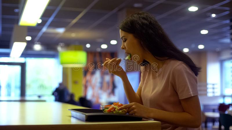 Female vegetarian eating fresh salad in restaurant, sitting table, healthy meal stock photo