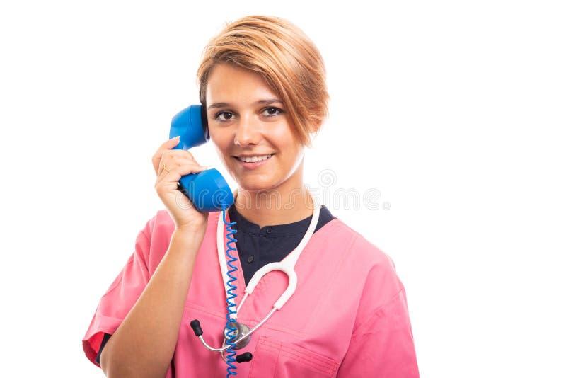 Female vet wearing pink scrub talking on blue receiver royalty free stock photos