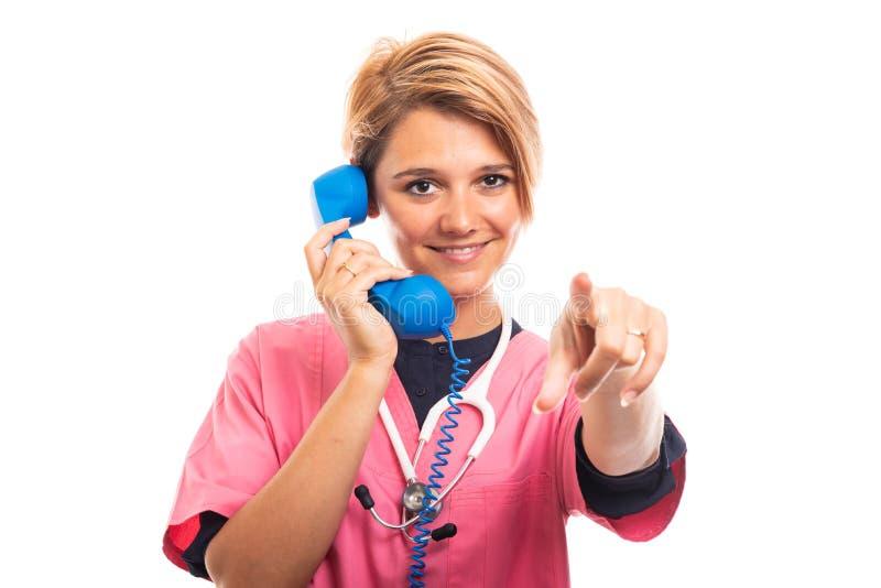 Female vet wearing scrub talking on blue receiver pointing finger. royalty free stock photo