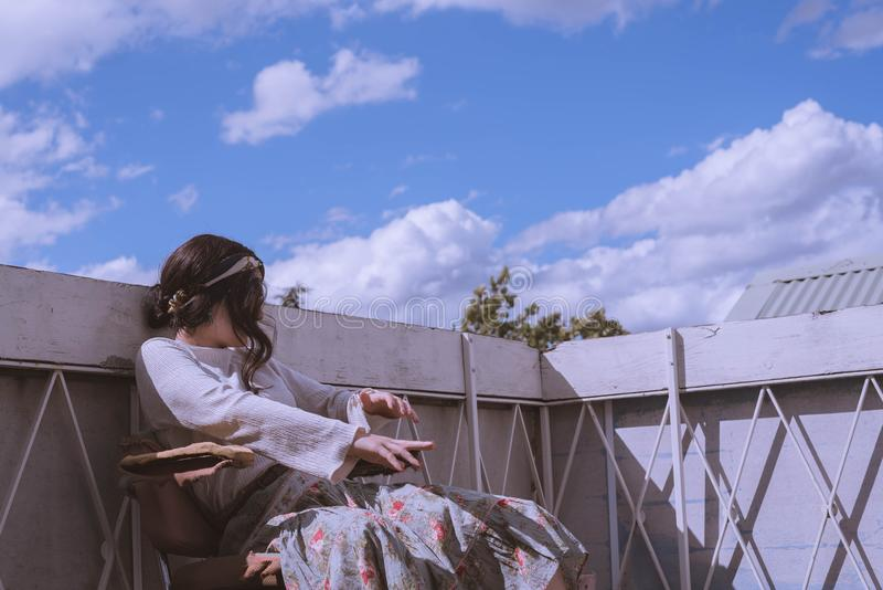 Female in a vintage dress sitting on the roof of a building with a beautiful blue sky and clouds stock image