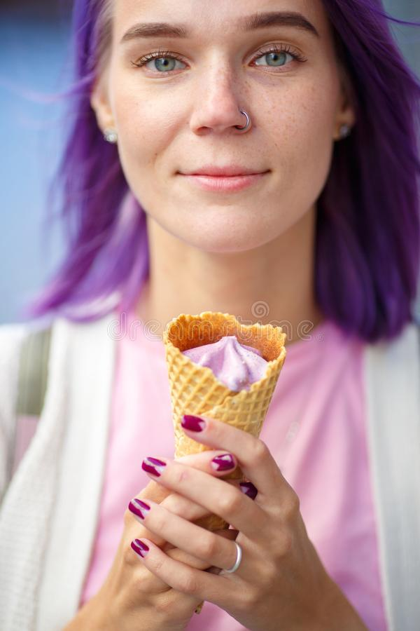 Female with violet hair holding in her hands purple ice cream. Female with gray eyes beautiful violet hair and pierced nose in white sweater and pink t-short stock photo