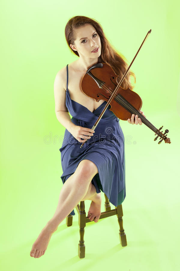 Female violinist. A beautiful female violinist over a green background royalty free stock photos