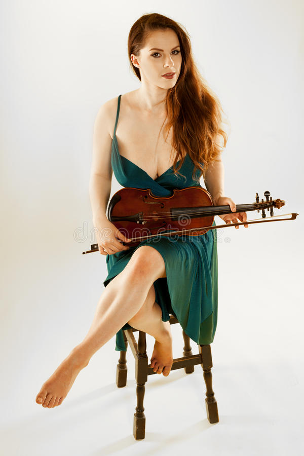 Female violinist. A beautiful female violinist over a light grey background royalty free stock images