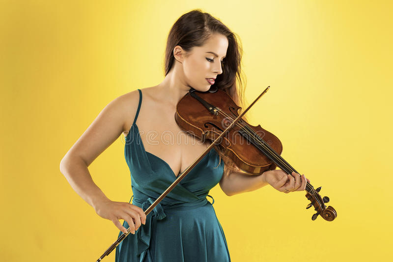 Female violinist. A beautiful female violinist over a yellow background royalty free stock photography