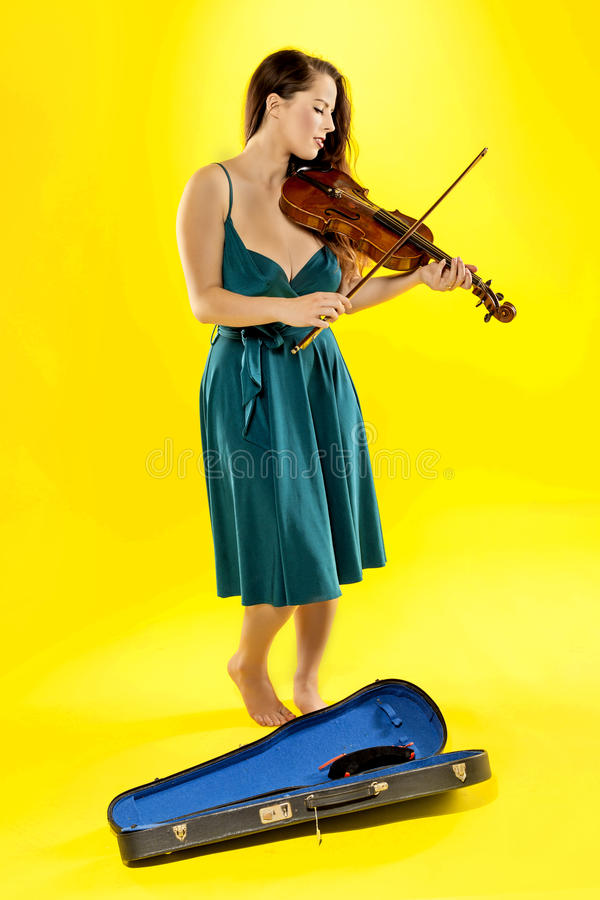 Female violinist. A beautiful female violinist over a yellow background stock photo