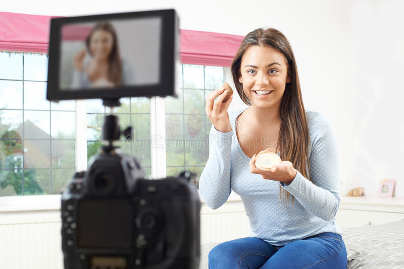 Female Vlogger Recording Broadcast About Make Up In Bedroom stock photography