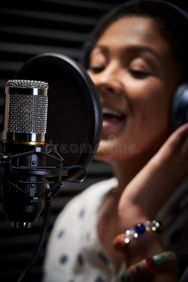 Female Vocalist Wearing Headphones Singing Into Microphone In Recording Studio stock photo