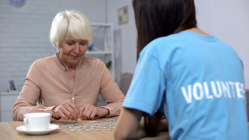 Female volunteer and aged woman collecting puzzles, Alzheimer disease awareness. Female volunteer and aged women collecting puzzles, Alzheimer disease awareness stock images