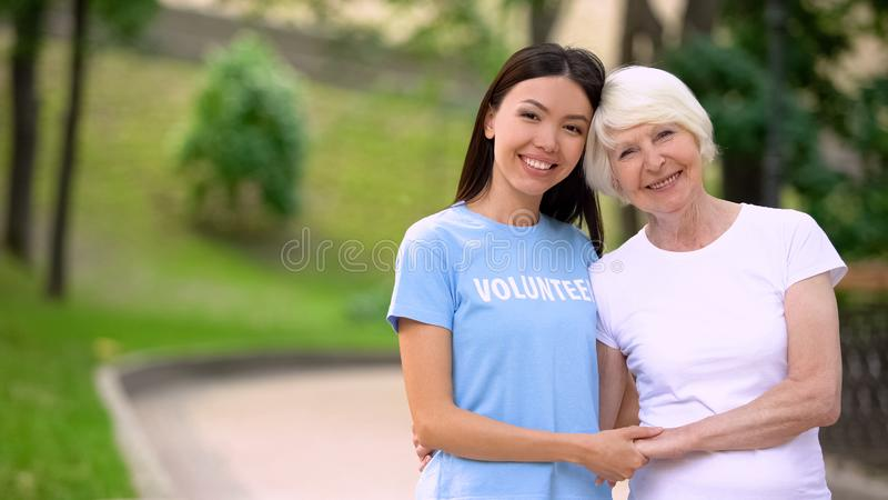 Female volunteer and happy elderly lady holding hands smiling camera, support. Stock photo royalty free stock photography