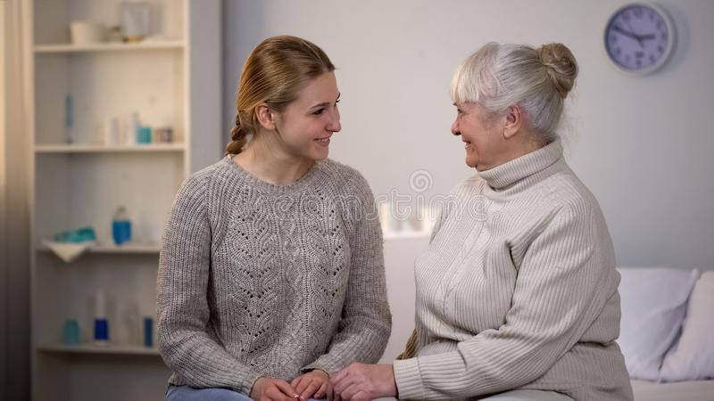 Female volunteer and happy retired lady looking each other sitting hospital bed royalty free stock photo