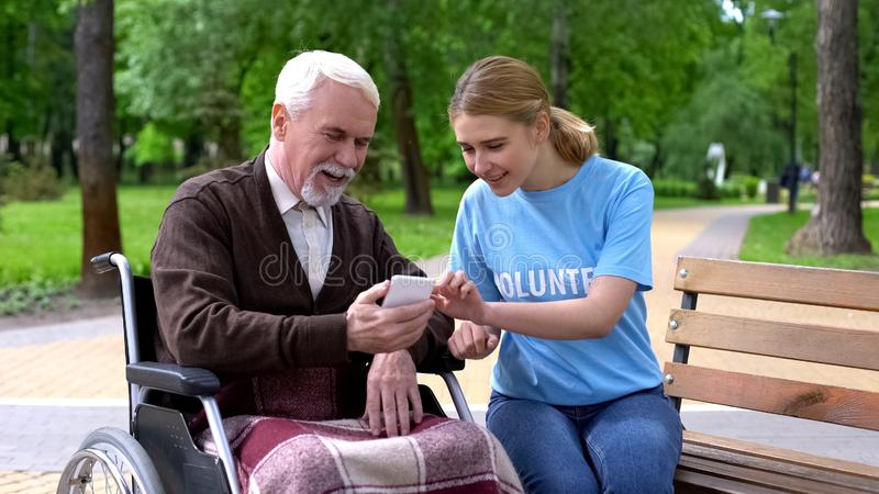 Female volunteer helping disabled old man use smartphone, nursing home charity. Stock photo stock photography