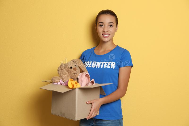 Female volunteer holding box with donations. On color background stock images