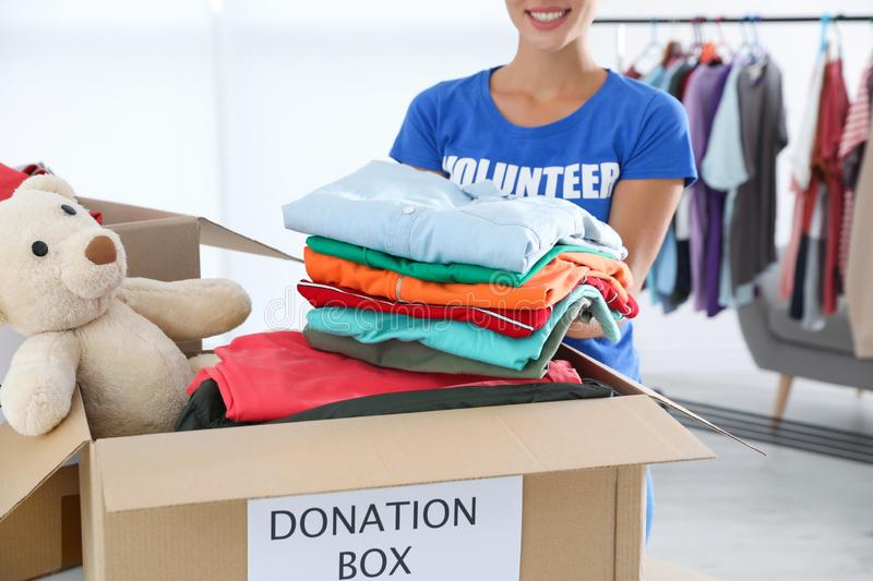 Female volunteer putting clothes into donation box stock image