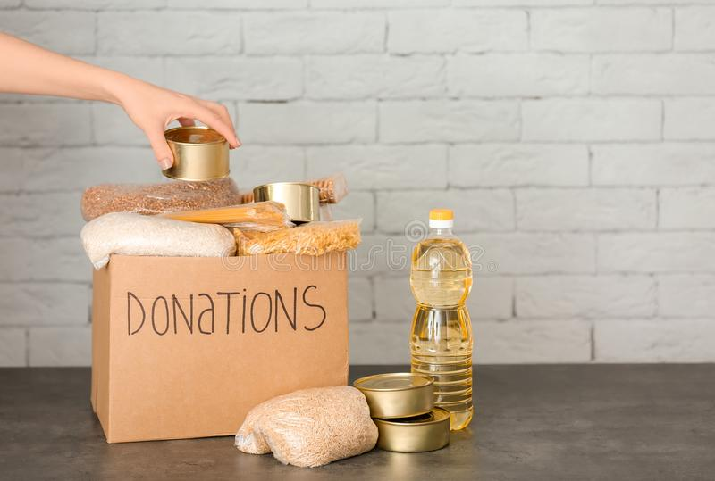 Female volunteer putting food into donation box royalty free stock photos
