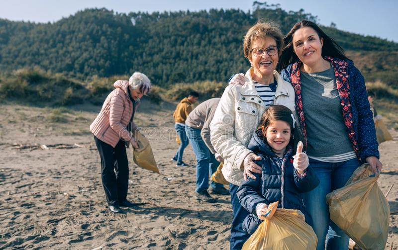 Female volunteers cleaning the beach stock photos
