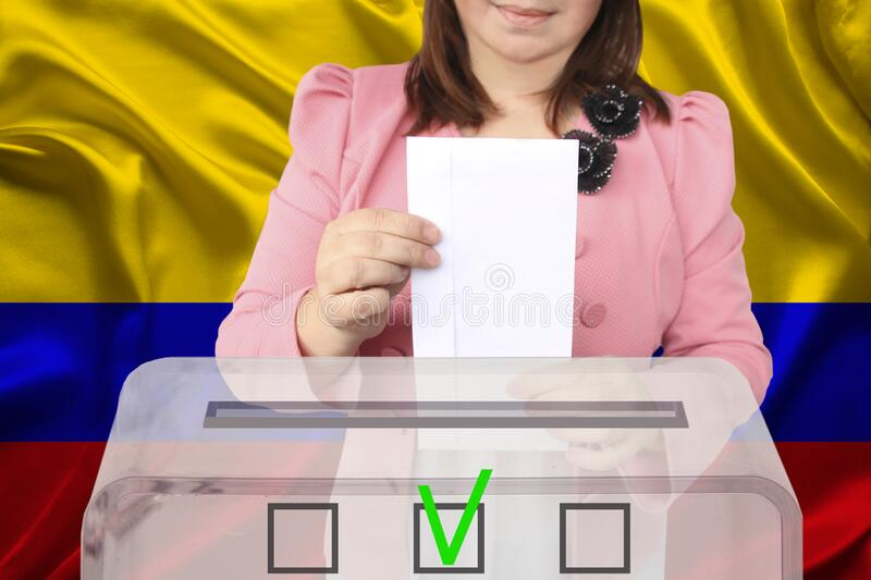 Female voter drops a ballot in a transparent ballot box against the backdrop of the Colombia national flag, concept of state. Elections, referendum royalty free stock images