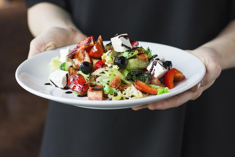 The female waiter holding in her hands plate with greek salad stock image