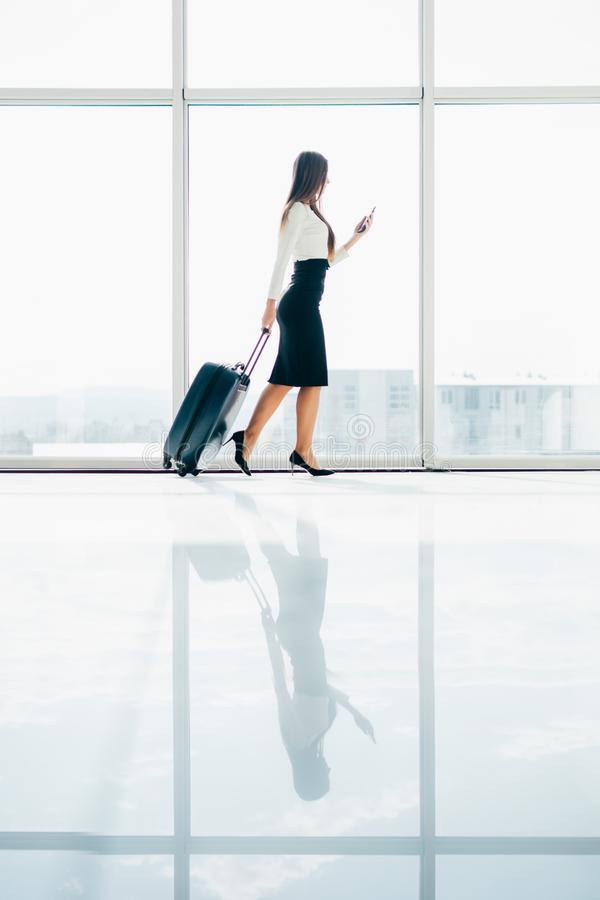Busineswoman walking through the airport using her smartphone device. stock photos