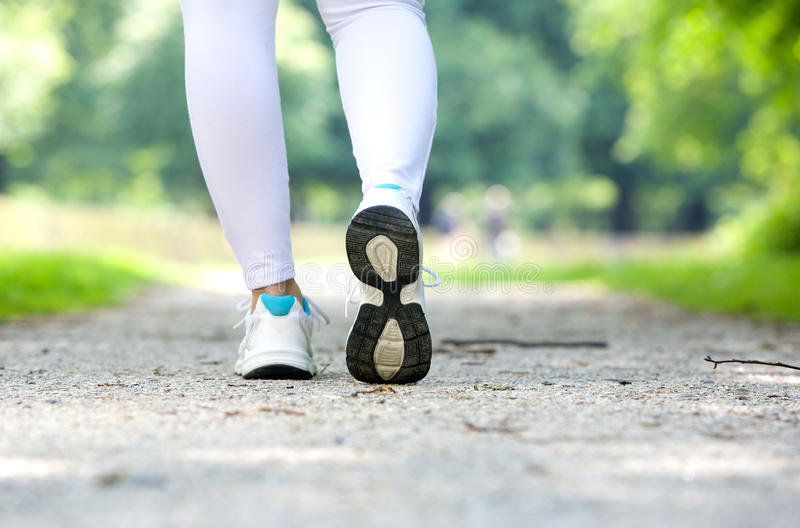 Female walking in running shoes outdoors stock photography