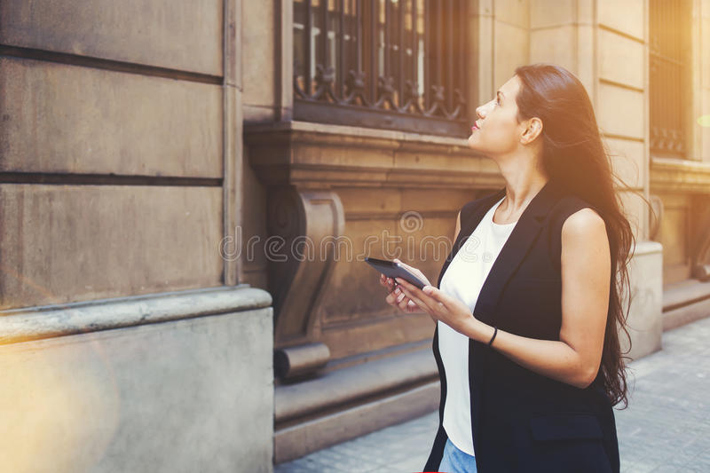 Female wanderer is using digital city map on her tablet computer during strolling outside stock images