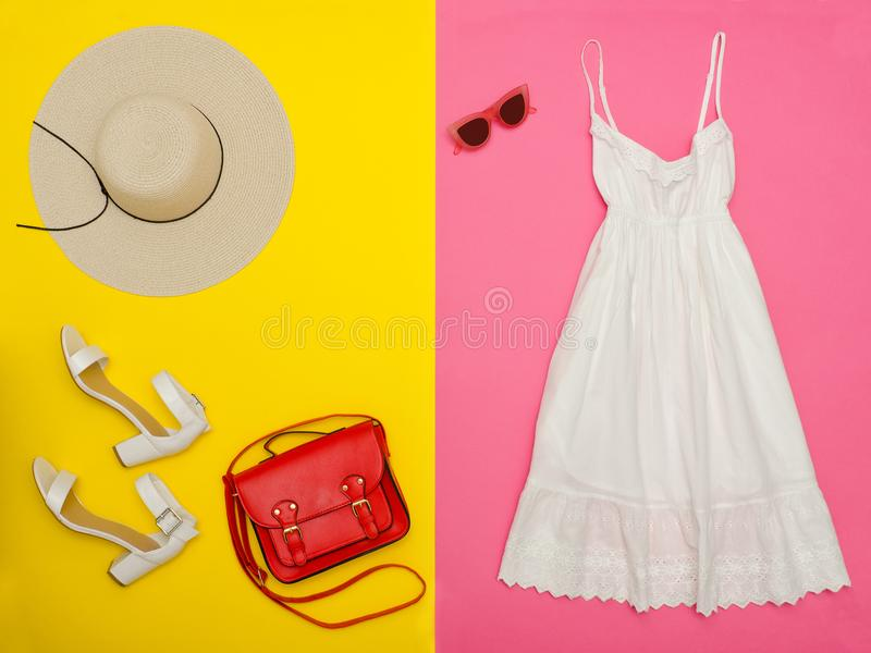 Female wardrobe. White sundress, handbag, white shoes and a hat. Bright pink-yellow background. stock images