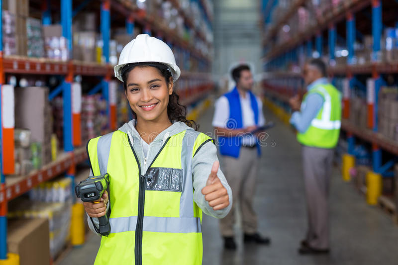 Female warehouse worker showing thumbs up sign stock photos