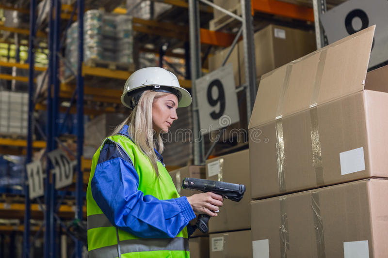 Female warehouse worker using scanner stock image