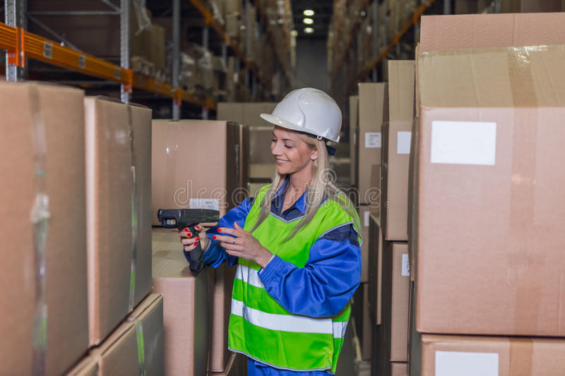 Female warehouse worker using scanner in storehouse royalty free stock images