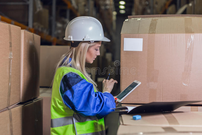 Female warehouse worker using tablet pc royalty free stock photography