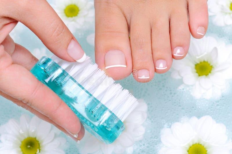 Female wash the toenails on foot. Female washes and cleans the toenails on foot in water stock images