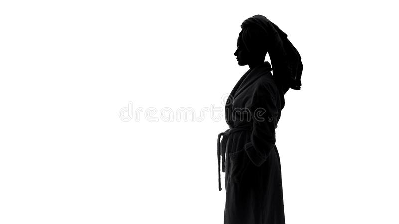 Female wearing bathrobe drying her hair with towel after morning shower, beauty royalty free stock image