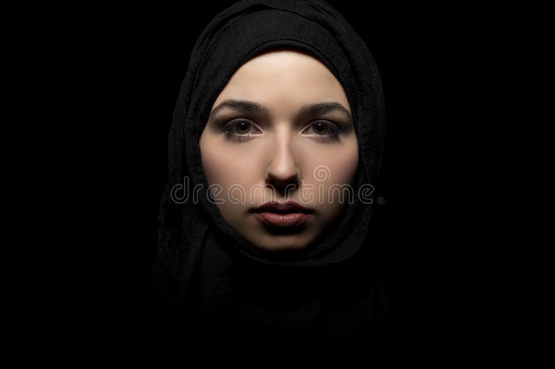 Female Wearing a Black Hijab. Proud and confident female wearing a black hijab as a conservative fashion choice to represent feminist freedom of expression and royalty free stock images