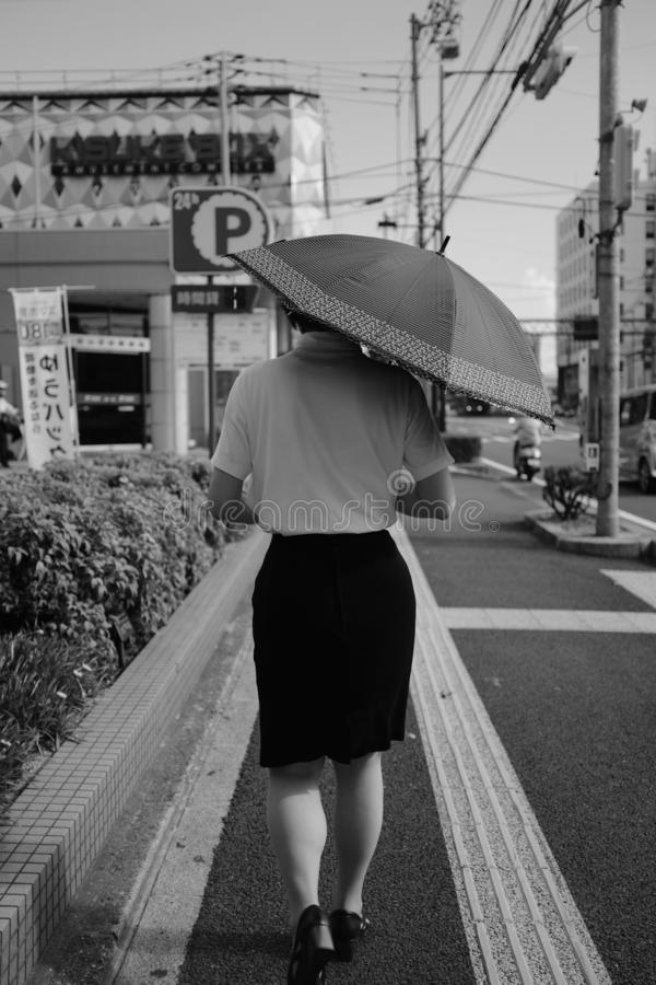 A female wearing black skirt with a shirt holding an umbrella walking on a sidewalk. MATSUYAMA, JAPAN - Jul 30, 2019: A grayscale vertical selective shot of a royalty free stock images