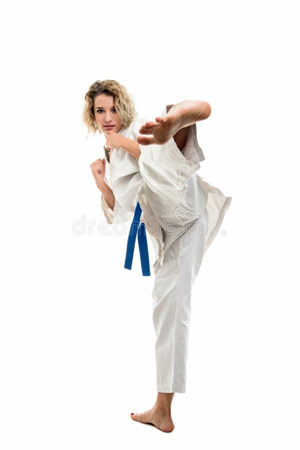 Female wearing martial arts uniform making karate move. Isolated on white background royalty free stock photos