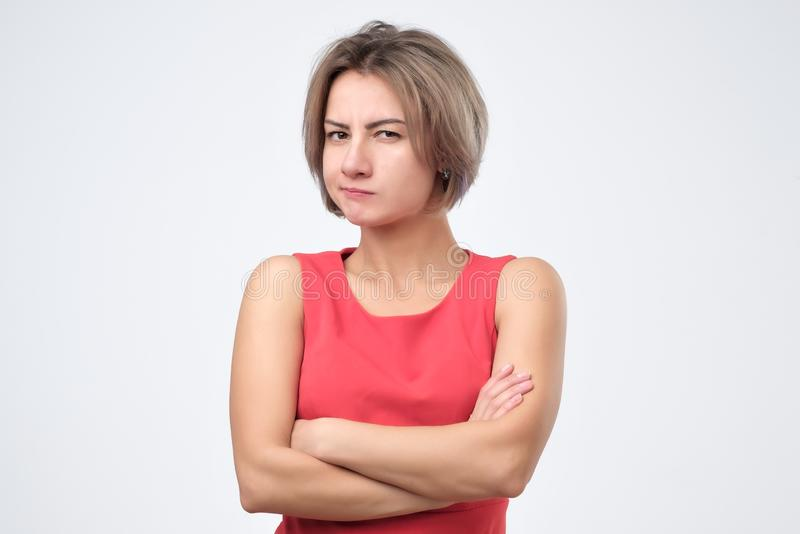 Female wearing red dress looking at camera, her eyes full of distrust and disappoinment. Serious young female wearing red dress looking at camera, her eyes full royalty free stock photos