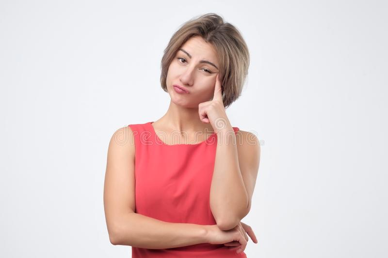 Female wearing red dress looking at camera, her eyes full of distrust and disappoinment. Serious young female wearing red dress looking at camera, her eyes full stock images