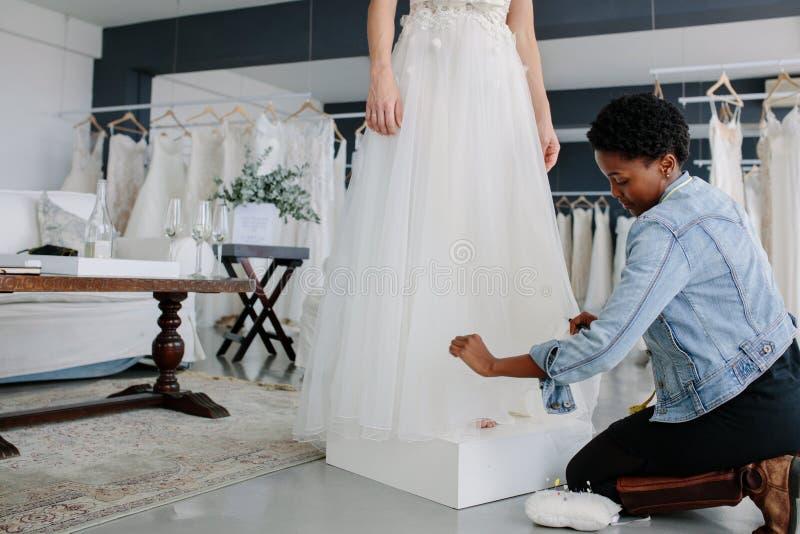 Female designer making adjustment to bridal gown. Female wedding dress designer making adjustment to bridal gown in her studio. Bride standing in her wedding royalty free stock photos
