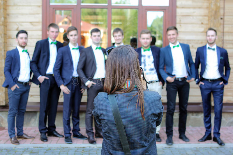 Female wedding photographer in action. Wedding photographer taking a picture of the groom and groomsmen stock photo