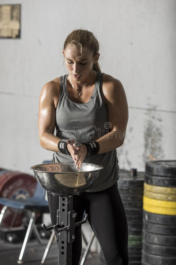 Female weight lifter preparing to lift by applying chalk to hands royalty free stock images