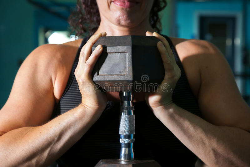 Female Weightlifter Goblet Squat Detail. Close up image of a dumbbell in a the hands of a female weightlifter in the goblet position royalty free stock image