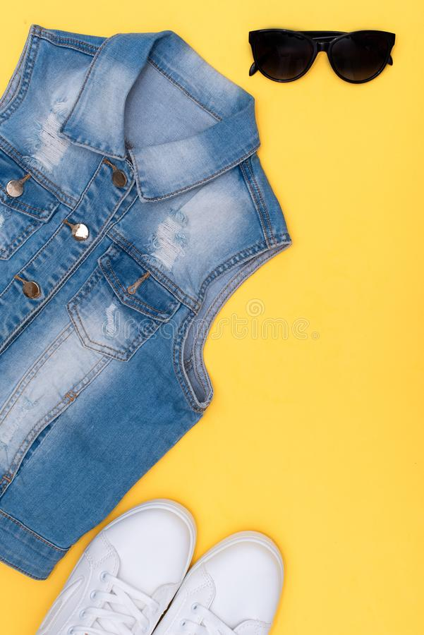 Female white sneakers and jeans on yellow background with copy space. Top view. Summer fashion, shopping, capsule wardrobe concept stock photo