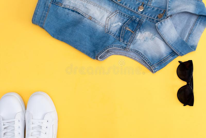 Female white sneakers and jeans on yellow background with copy space. Top view. Summer fashion, shopping, capsule wardrobe concept. Creative flat lay. Modern stock image