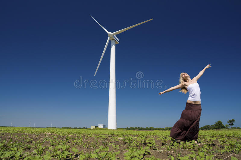 Female at wind power generator royalty free stock image