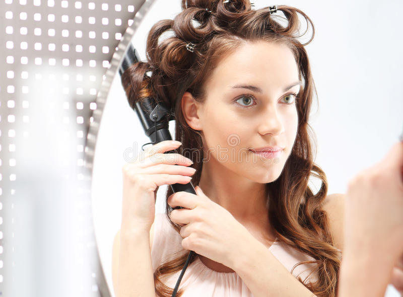Female winds hair on rollers. Young girl winds up hair curling iron standing in front of the bathroom mirror stock images
